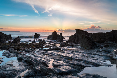 treacherous: Low tide and sunrise at the beach at Looe in Cornwall Stock Photo