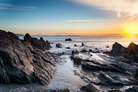 Sunrise at a rock beach at Looe in Cornwall