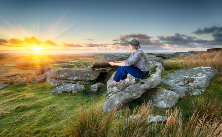 cornish: Woman out hiking, relaxing and using a tablet pc at sunset on a rocky tor on Bodmin Moor in Cornwall