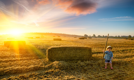 Toddler at sunrise in a field of fresh haystacks photo
