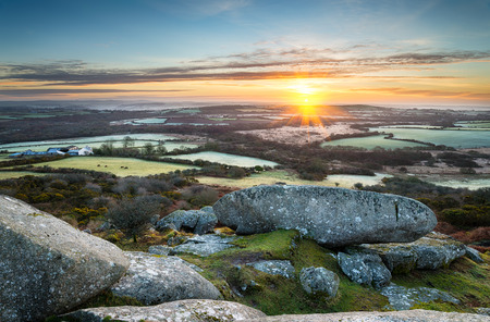 A frosty early spring sunrise looking out over a patchwork of fields and rolling hills at Helman Tor a rocky outcrop of rugged moors near Bodmin in Cornwall