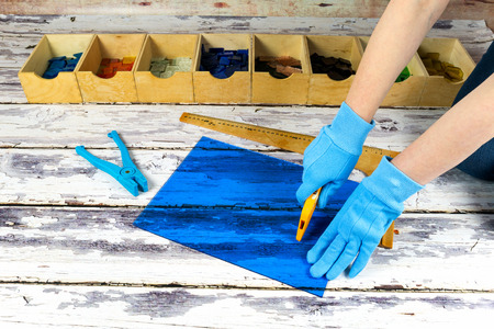 Artist cutting sheets of stained glass into small mosaic squares