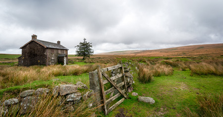 A derelict and abandoned farmhouse at Nuns Cross a remote part of Dartmoor National Park near Princetown in Devon  photo