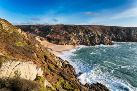 The sandy beach and high cliffs at Porthcurno near Penzance in Cornwall Stock Photo