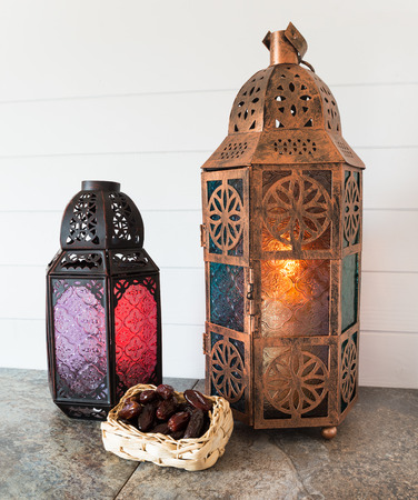 Bronze and glass metal lanterns with a basket of dates photo