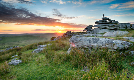 bodmin: The silhouette of a lonely figure enjoying the sunset on top of a tor on Bodmin Moor in Cornwall Stock Photo