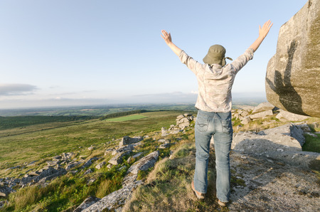 woman hiking: Woman wearing hat with arms outstretched standing on Kilmar Tor a high peak on Bodmin Moor in Cornwall