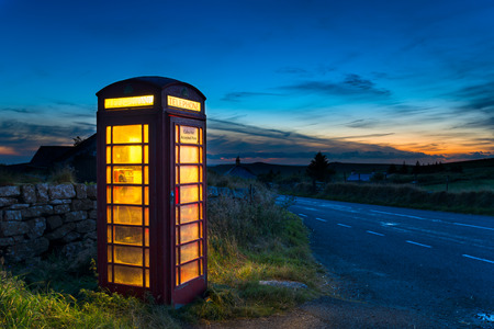 Old red phone box at dusk on a country road in Dartmoor, Devon