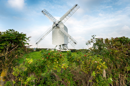 hedgerow: Chillenden Windmill in the Kent countryside, an open trestle post mill Stock Photo
