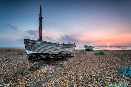 beach shingle: Bella alba sopra vecchie barche in legno su una spiaggia di ciottoli