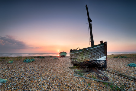 Old fishing boats on a shingle beach in Kent photo