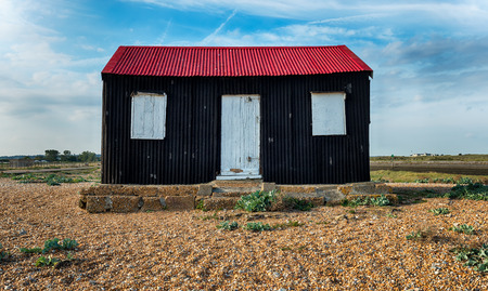 fishing hut: An old fishing hut with a red tin roof on the shore at Rye in East Sussex