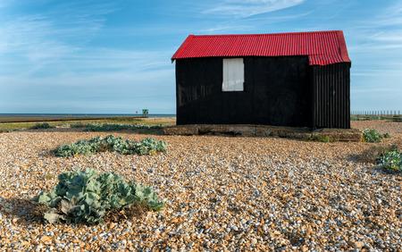beach shingle: Una capanna nero con un tetto di lamiera rossa su una spiaggia di ciottoli a Rye in East Sussex Archivio Fotografico