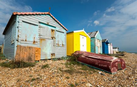 beach shingle: Una fila di cabine colorate su una spiaggia di ciottoli a St Leonards On Sea a Hastings, East Sussex Archivio Fotografico