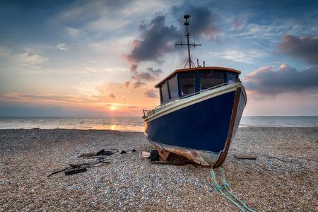 A blue fishing boat under a beautiful sunrise on a shingle beach photo