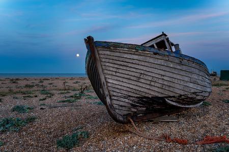 shingle beach: An old wooden fishing boat on a shingle beach under a full moon