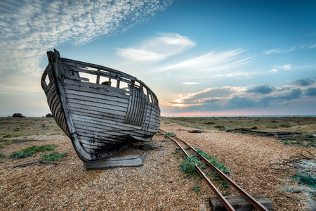 Old wooden fishing boat stranded on a shingle beach photo