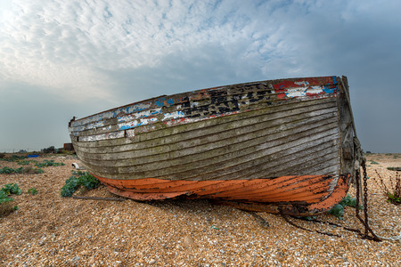 shingle beach: An old abandoned wrecked wooden fishing boat high on a shingle beach