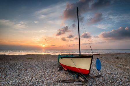 beach shingle: Barca a vela in una bella alba su una spiaggia di ciottoli