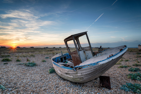 beach shingle: Un vecchio abbandonato peschereccio di legno con le reti lavato su una spiaggia di ciottoli