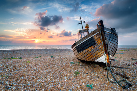 Beautiful sunrise over an old wooden fishing boat on a pebble beach