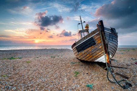 barca da pesca: Bella alba sopra una vecchia barca da pesca in legno su una spiaggia di ghiaia