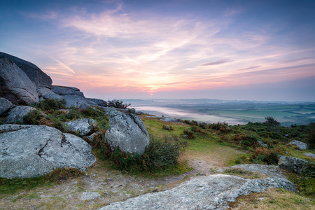 A misty morning sunrise at Helman Tor in Cornwall photo