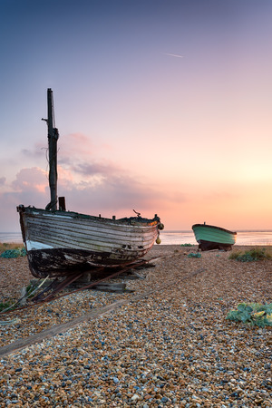 kent: Beautiful sunrise over old wooden boats on a shingle beach in Lydd, Kent
