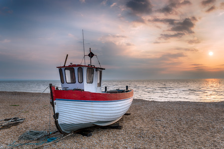 A red and white wooden fishing boat on the beach just after sunrise Stock fotó