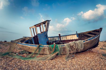beach shingle: Vecchia barca da pesca in legno lavata in su su una spiaggia ghiaiosa Archivio Fotografico