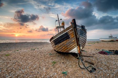A beautiful sunrise over a wooden fihing boat on s shingle beach photo