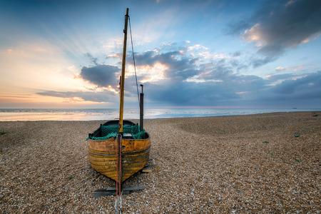 beach shingle: Una piccola barca a vela di legno su una spiaggia di ghiaia sunrise Archivio Fotografico