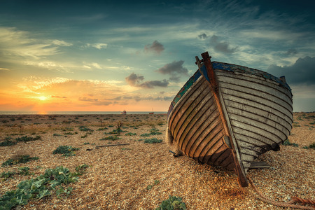 A beautiful sunrise over a wooden fihing boat on s shingle beach