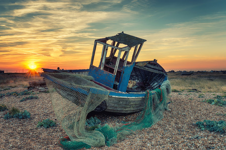An old abandoned wooden fishing boat with nets washed up on a shingle beach, vintage effect photo