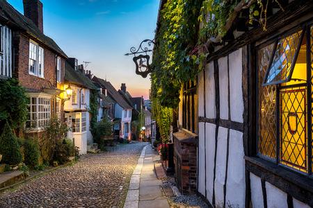 Schemer bij een rij van mooie oude huizen op een geplaveide straat in Rye, East Sussex