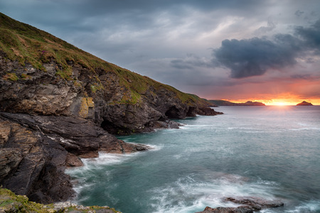quin: Steep rugged cliffs, sea caves and high waves at Epphaven a small rocky cove between Lundy Bay and Port Quin in Cornwall Stock Photo