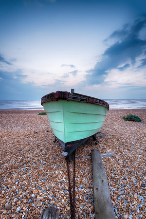 A green fishing boat on a pebble beach at Lydd on Sea in Kent photo