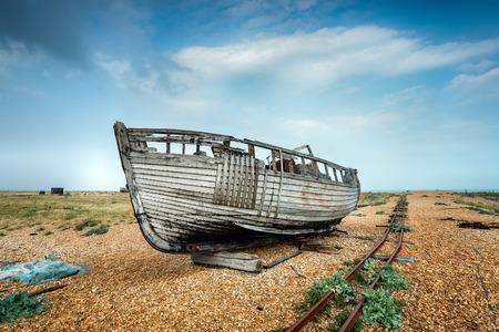 beach shingle: Una vecchia barca di legno accanto a una vecchia linea ferroviaria su una spiaggia di ciottoli