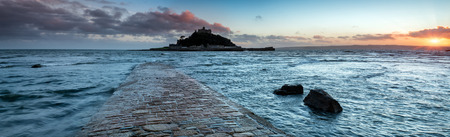 Panoramic view of the causeway at high tide leading to St Michaels Mount at Marazion near Penzance in Cornwall photo