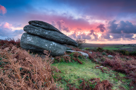 bodmin: Sunrise over a large granite boulder on rugged moorland at Helman Tor near Bodmin in Cornwall
