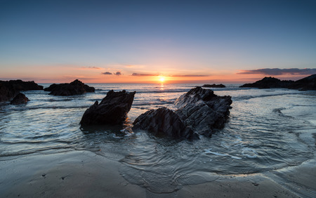 Sunset over rocks at Freathy beach in Whitsand Bay in Cornwall