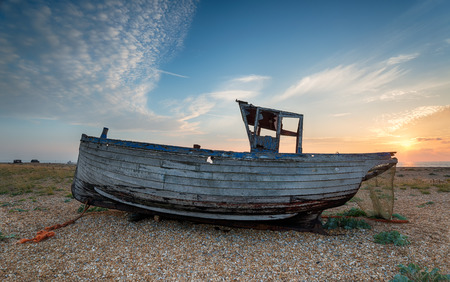 shingle: An old wrecked fishing boat grounded on a shingle beach in Kent under a sunrise sky