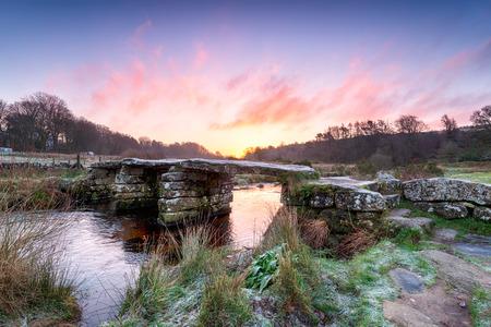 granite park: A frosty winter sunrise over an old granite clapper bridge at Postbridge on Dartmoor National Park in Devon
