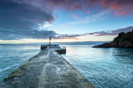 south coast: Dramatic sunrise over the pier at Looe on the south coast of Cornwall Stock Photo