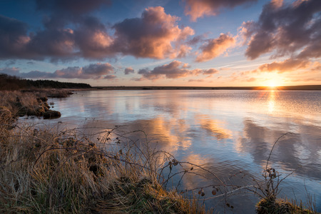 A beautiful dramatic winter sunrise over Crowdy Reservoirnear Davidstow on Bodmin Moor in Cornwall photo