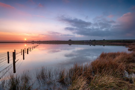 bodmin: Beautiful sunset over Dozmary Pool the only natural lake on Bodmin Moor in Cornwall and steeped in Arthurian legend Stock Photo