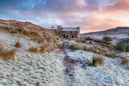 willy: A beautiful frosty winter sunrise over an old abandoned farmhouse on Bodmin Moor in Cornwall with Brown Willy in the background Stock Photo