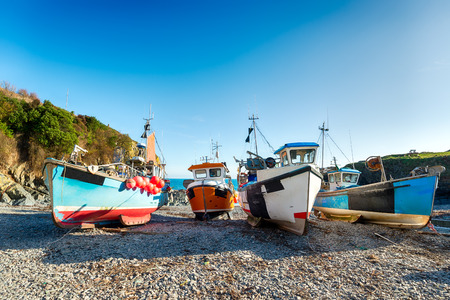 Colourful fishing boats on the beach at Cadgwith on the Lizard in Cornwall photo
