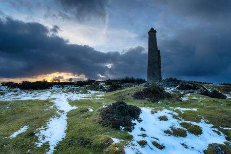 Storm clouds gather over an abandoned chimney stack left over from copper mining at Darite on Bodmin Moor in Cornwall