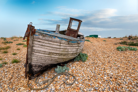 shingle: A weathered old wooden fishing boat on a shingle beach